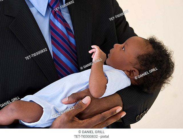 Businessman holding baby