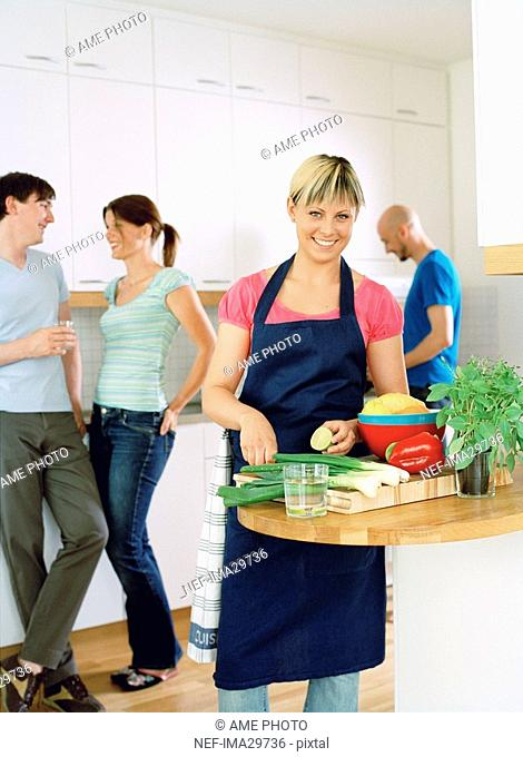 Four people preparing food in a kitchen