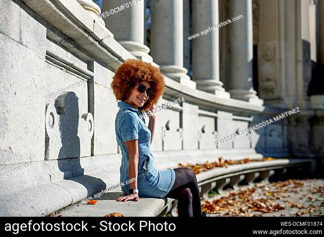 Smiling woman with hand in hair at Alfonso Xii Monument, Parque Del Buen Retiro, Spain