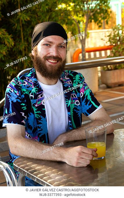 portrait of happy young man with beard and headscarf while having a soda on a terrace