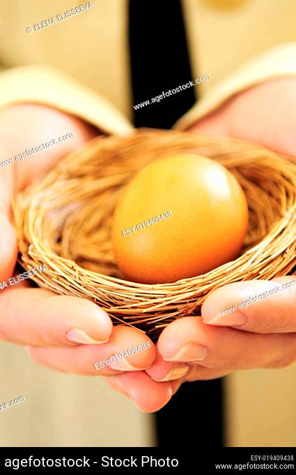 Hands holding nest with egg
