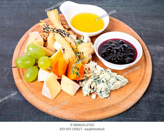 Cheese platter with honey and berry jam. Plate located on a black table as a background