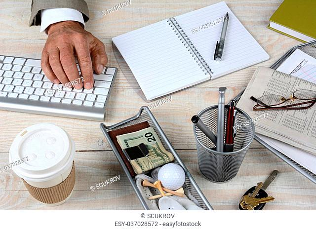 Closeup of a businessman's desk. The white rustic wood desk has a keyboard, coffee cup, keys, notebook, glasses, pencil cup