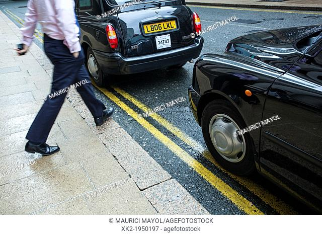 Businessman crossing the street between to Black Cab in Canary Wharf, London, UK
