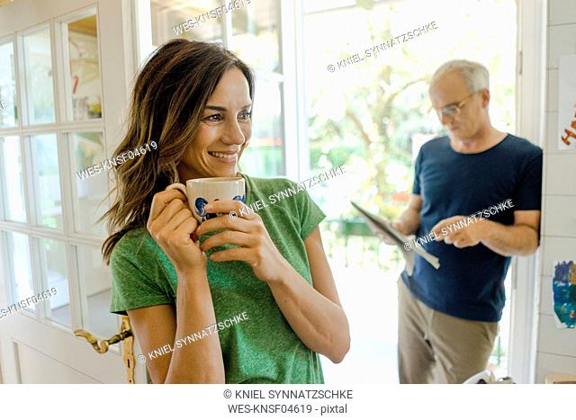 Mature couple at home with woman drinking coffee and man reading newspaper