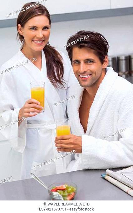 Lovely couple wearing bathrobes and holding glass of orange juice