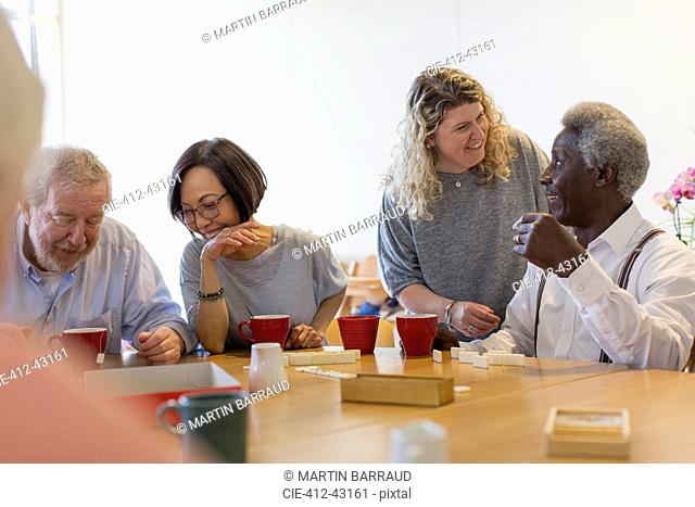 Volunteer talking with senior man playing games at table in community center