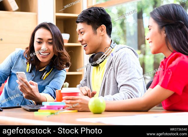 Successful professional team of web designers smiling while testing responsive layout on both mobile phone and desktop PC