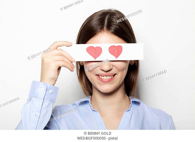 Young woman covering part of face with painted hearts