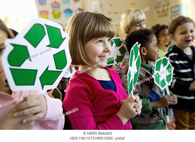 Girl holding recycling symbol in school