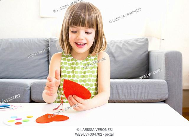 Portrait of embroidering little girl at home