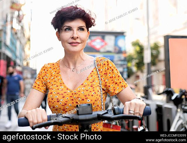 Mature woman on push scooter in city