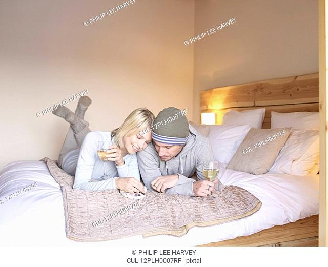 woman and man lying on bed eating