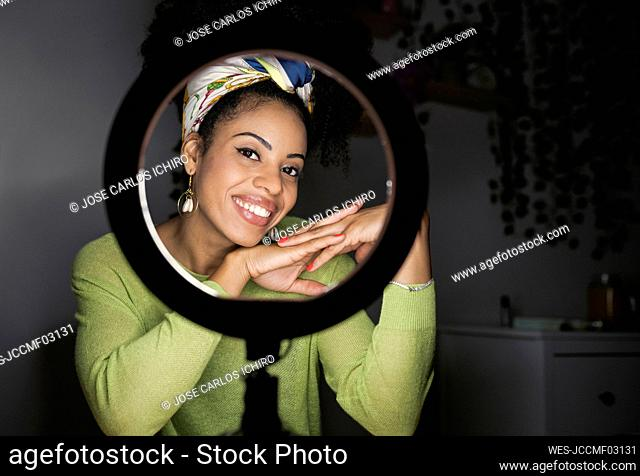Smiling woman wearing headband looking through illuminated ring light