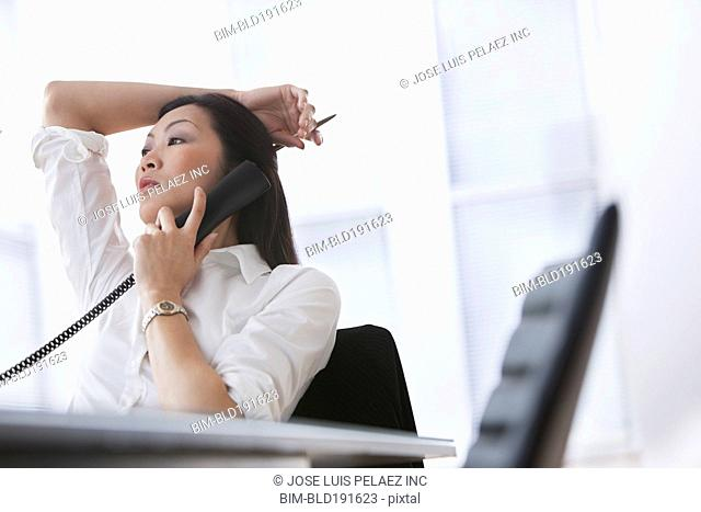 Chinese businesswoman using telephone in office