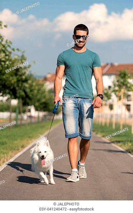 Young Man And German Spitz Walk In The Park - He Keeps The Dog On The Leash