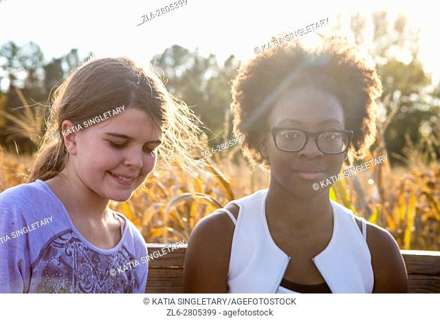 A Beautiful young African American teenager with black glasses is smiling at the camera with the sun rays shining though her wild hair