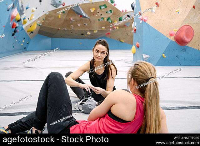 Two women having a break in climbing gym