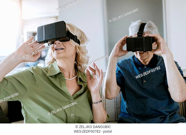 Senior couple at home sitting on couch wearing VR glasses