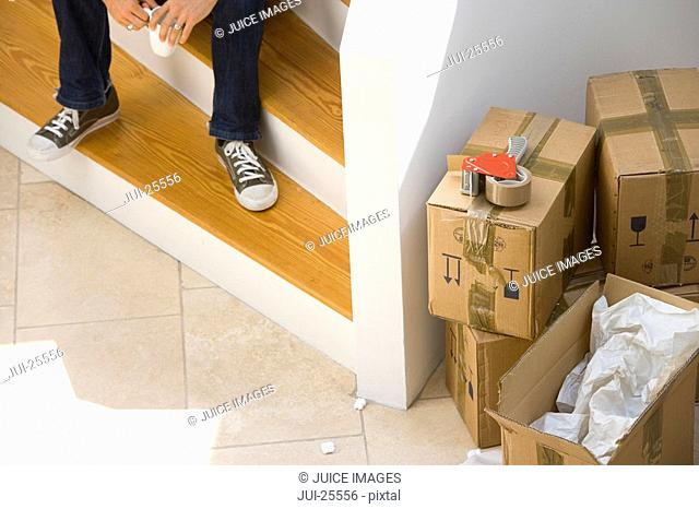 Man sitting on staircase near stack of moving boxes