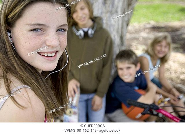 Portrait of a teenage girl smiling with her friends sitting behind her