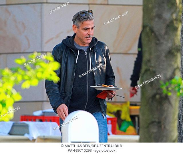 US actor George Clooney holds a plate with grilled meat as he attends a barbecue at the hotel 'Zu den Rothen Forellen' in Ilsenburg, Germany, 21 May 2013