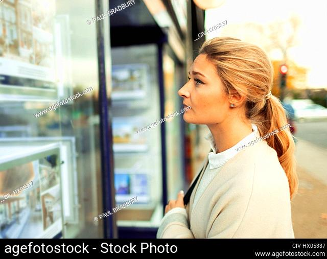Young woman looking at house listings in storefront