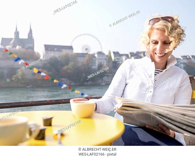Switzerland, Basel, smiling woman reading newspaper in a street cafe at River Rhine