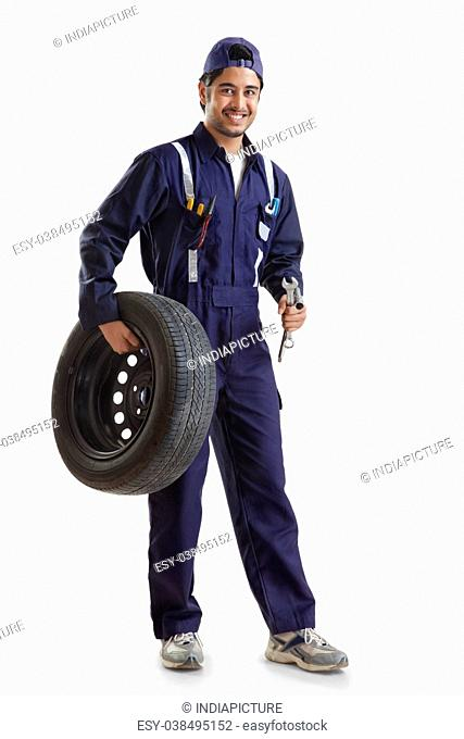 Portrait of car mechanic with spare tyre and hand tools