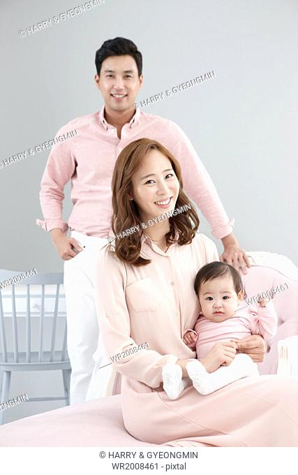 a couple posing with a baby in a portrait