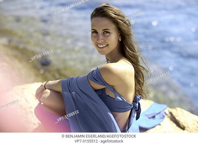 Woman in blue dress, sitting by the sea, Crete, Greece