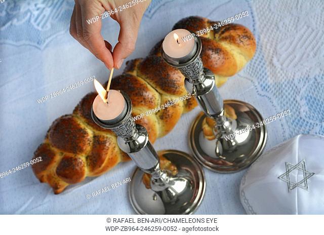 Shabbat eve table.Woman hand lit Shabbath candles with uncovered challah bread and kippah.Photo by Rafael Ben-Ari/Chameleons Eye