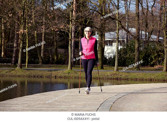 Full length front view of woman nordic walking by pond