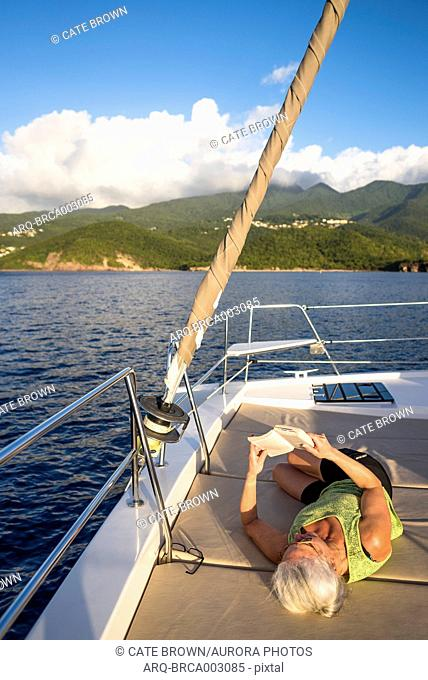 Mature woman with gray hair reading book while lying on deck of sailboat, Bouillante, Basse Terre, Guadeloupe