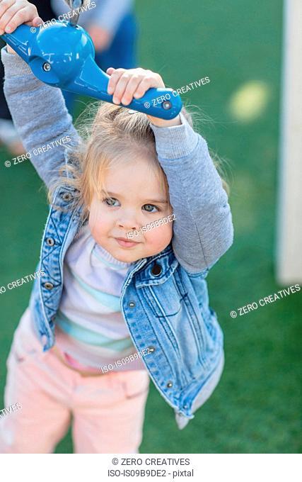 Girl at preschool, holding playground rope swing in garden