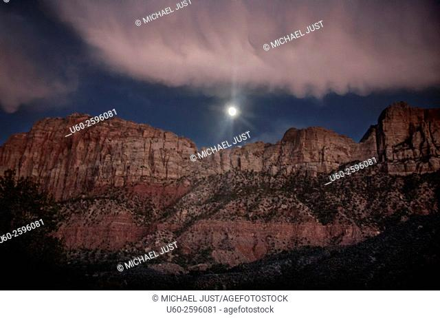 A full moon rises through the clouds and over the rim of Zion Canyon at Zion National Park, Utah