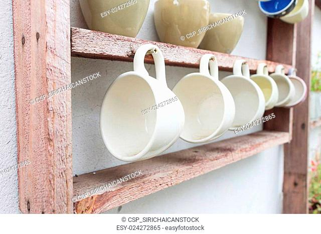 White coffee cup hanging on wooden shelf