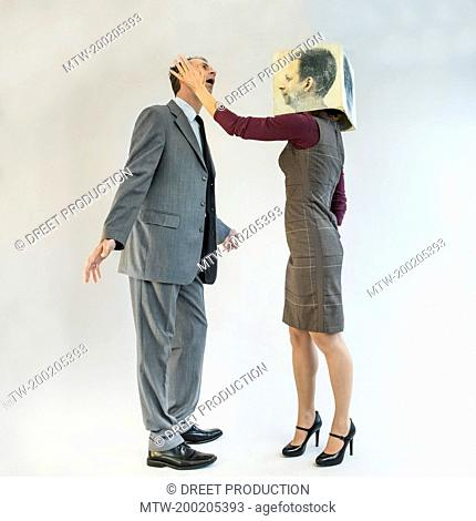 Businessman getting slapped by businesswoman wearing mask