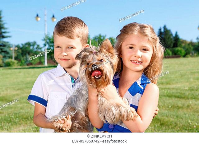 Little family. Upbeat nice little children holding the dog and bonding to each other while expressing joy