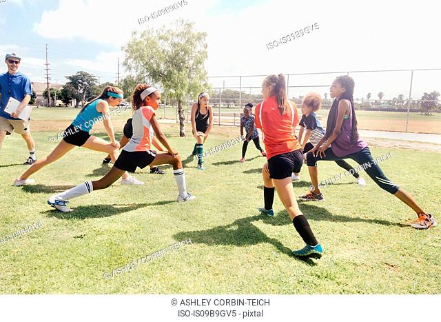 Teacher instructing schoolgirl soccer players in warm up on school sports field