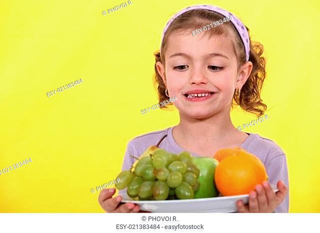 Little girl holding plate of fruit