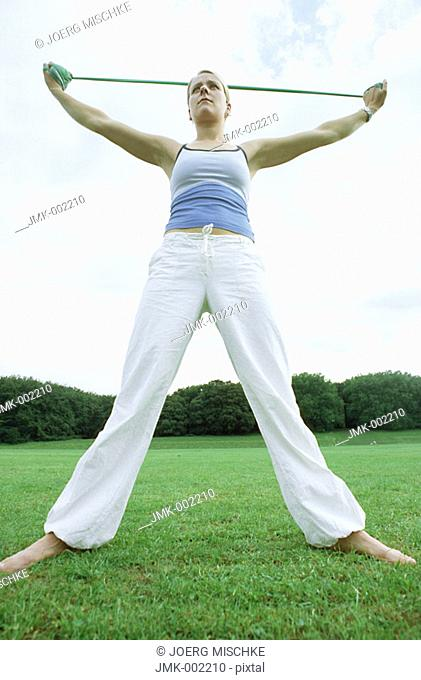 A young woman, 15-20 20-25 25-30 years old, making exercises with an elastic band, making gymnastics