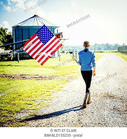 Caucasian girl waving American flag on farm