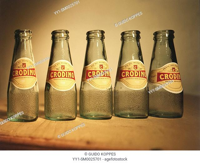 Rotterdam, Netherlands. Assignment Technical Camera or TC, by Photo Academy, of five Crodino bottles without liquid on a wooden table