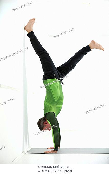 Man doing his fitness regime, practising handstand