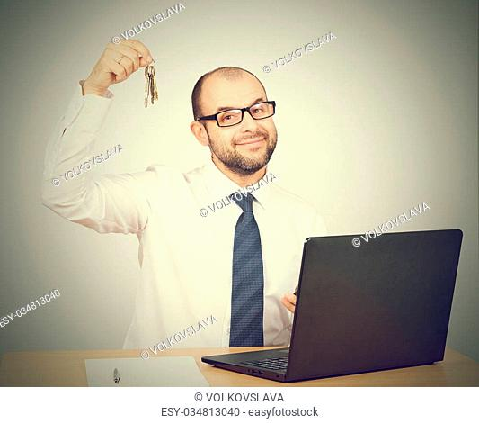 Man realtor offering keys. Isolated on gray background