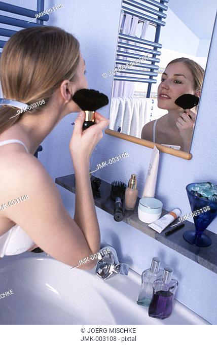 A young woman, 20-25 25-30 years old, in the bathroom, putting powder on her face in front of a mirror