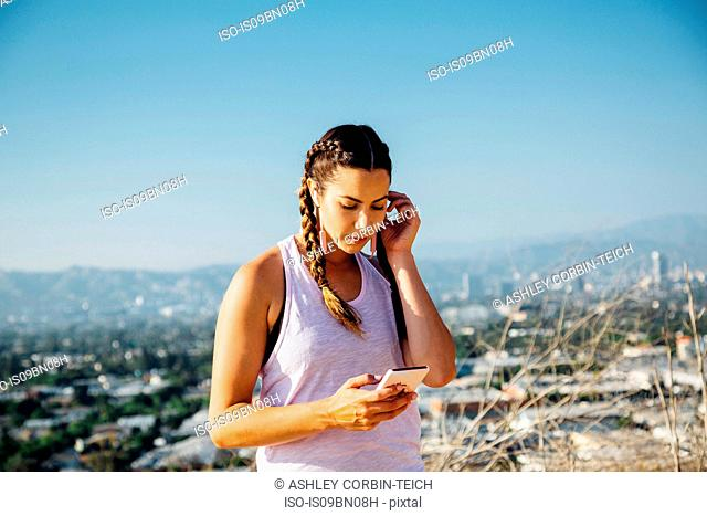Woman using cellphone on hilltop, Los Angeles, US