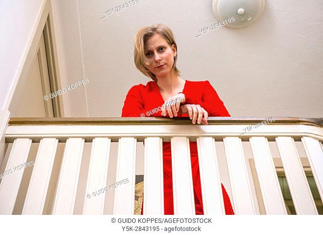 Tilburg, Netherlands. Young adult caucasian woman wearing a red dress leaning over a stair ballustrade