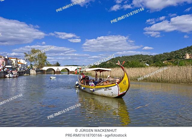 Historical fishing boats as tourist boats with Ponte Velho over Rio Arade in Silves city, Algarve, Portugal, Europe